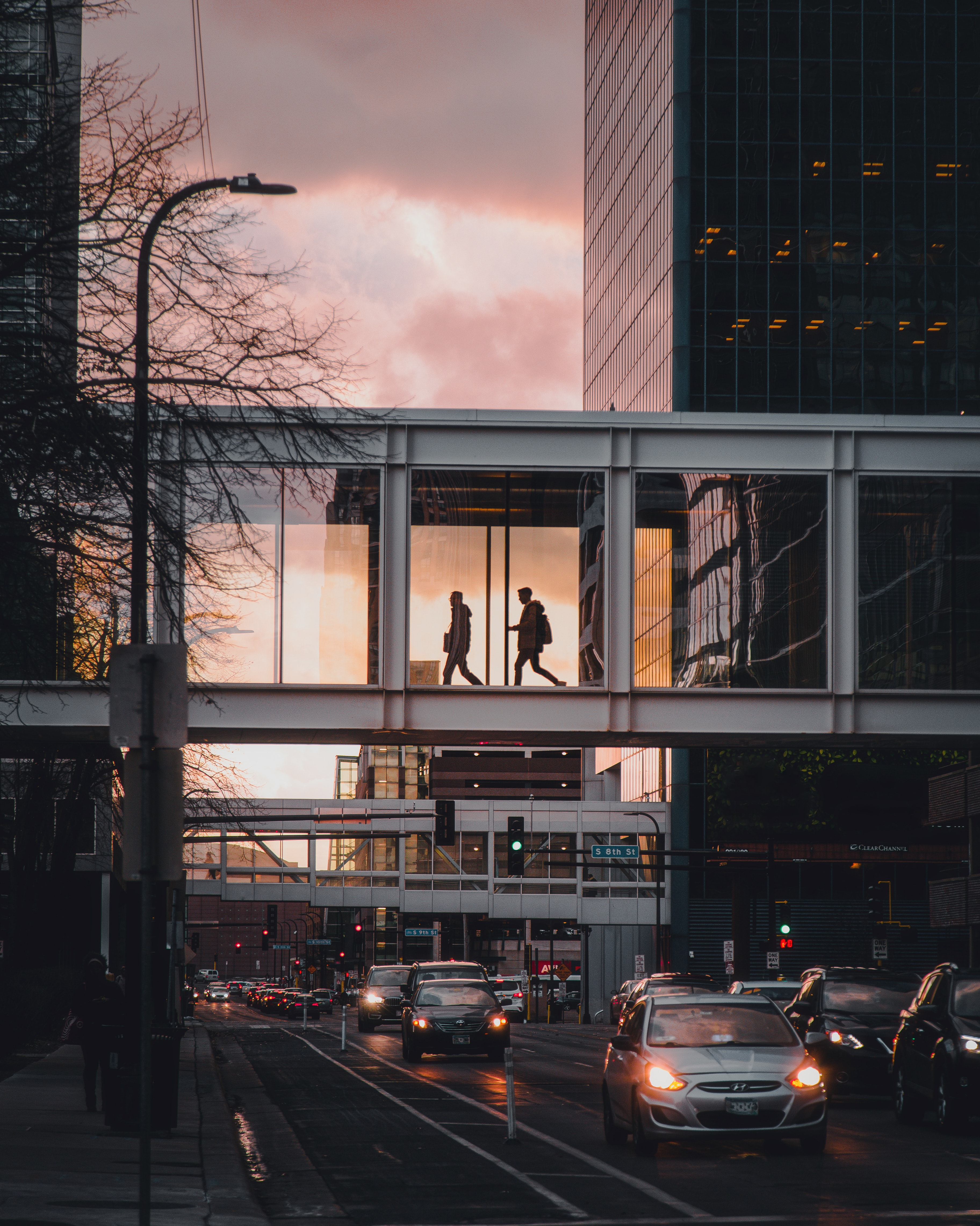 People in above-ground walkway at dusk